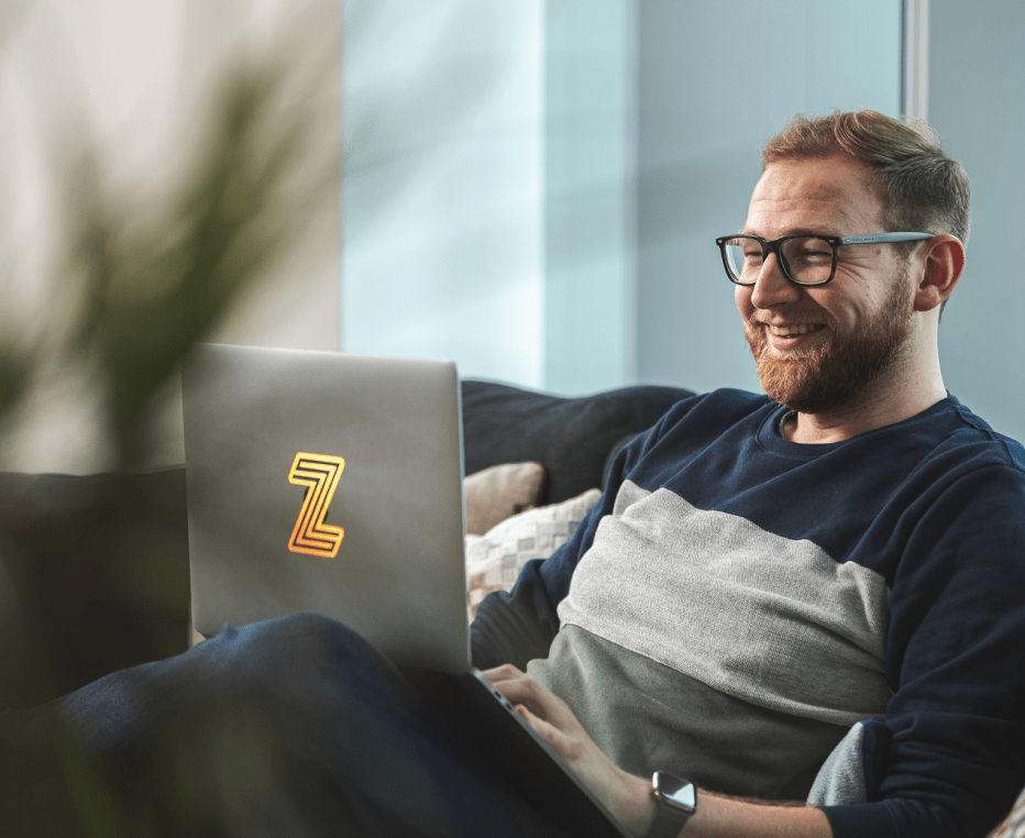 30 year old male customer experience expert sitting on his sofa at home and smiling