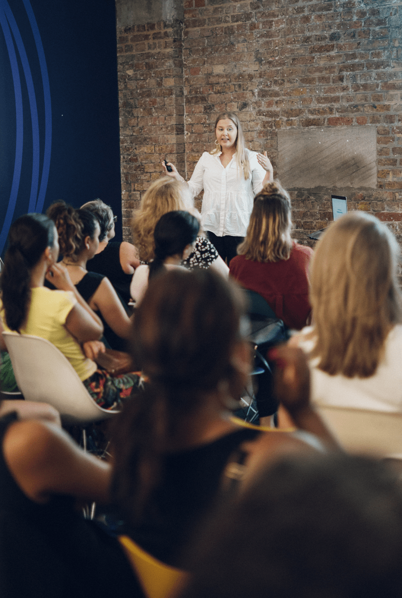Female customer experience expert talking in front of an audience